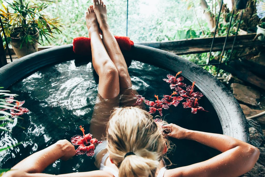 Woman,Relaxing,In,Round,Outdoor,Bath,With,Tropical,Flowers.,Organic