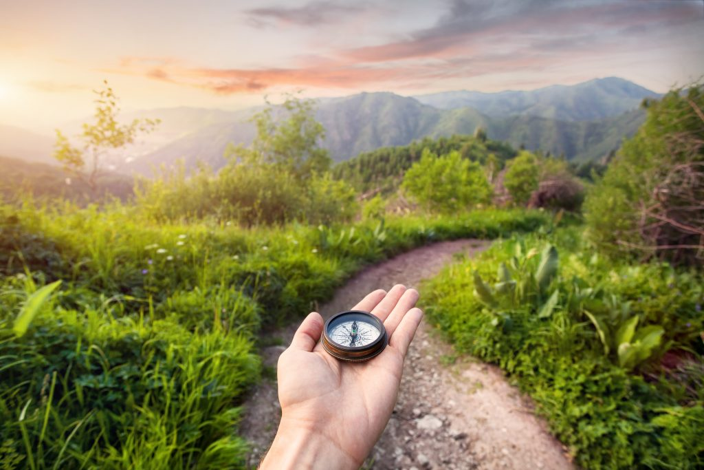 Hand,With,Compass,At,Mountain,Road,At,Sunset,Sky,In