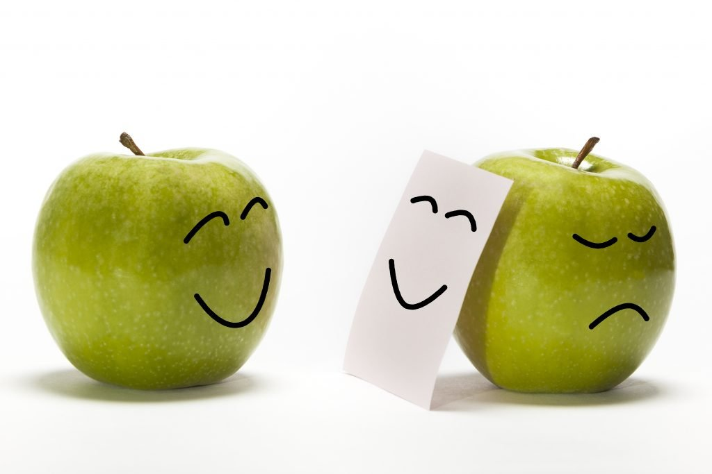 An apple smiling to other one, that is concealing its sadness behind a smily mask